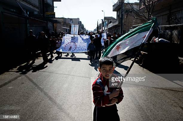 A young boy carries the Syrianrebel adopted flag during an antiregime demonstration in the Syrian village of alQsair 25 km southwest of the...