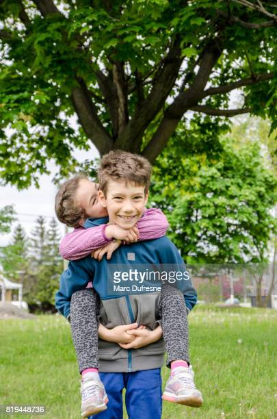 young boy carrying his sister on his back while she's kissing him - sister stock pictures, royalty-free photos & images