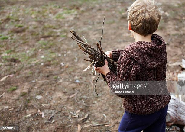 Young boy carrying sticks for campf