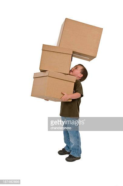 Young boy carrying three moving boxes
