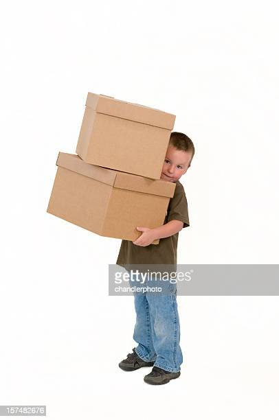 Young boy carrying two moving boxes