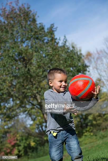 young boy catching red football happy - dreiviertelansicht stock pictures, royalty-free photos & images