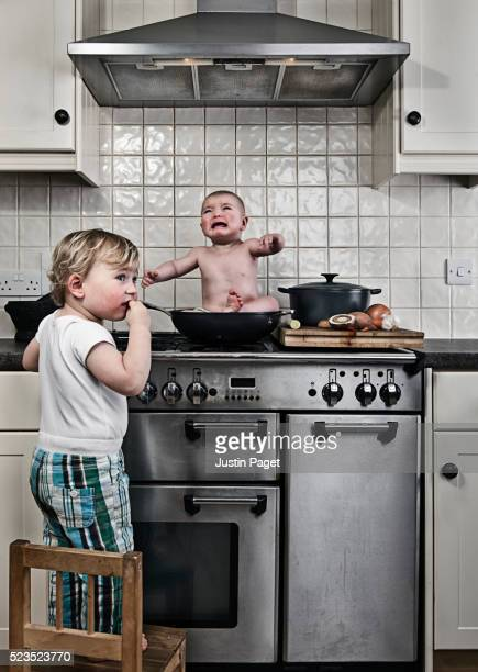 Young boy (3-4) caught cooking baby brother (1-6 months) on stove