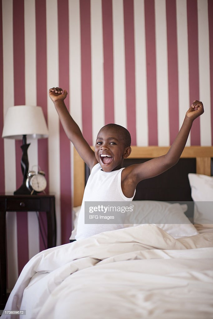 Young boy cheerfully getting out of Bed, Cape Town, South Africa : Stock Photo