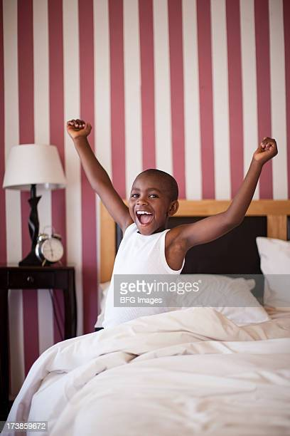 Young boy cheerfully getting out of Bed, Cape Town, South Africa