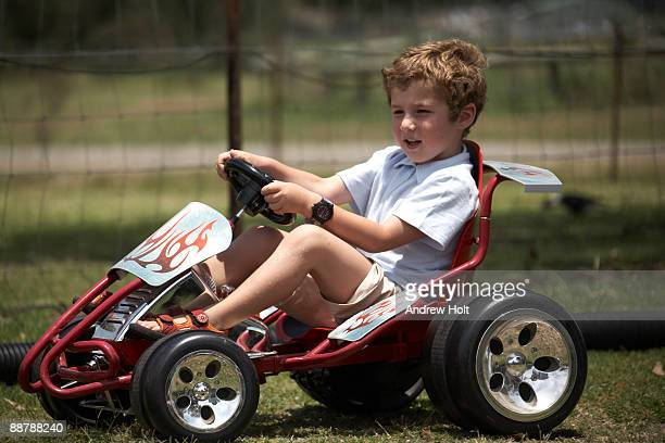 Young boy child driving red Go Kart car