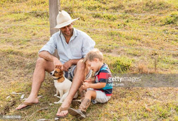 young boy child with his dad and terrier dog sitting near a fence post on the farm - thisisaustralia stock pictures, royalty-free photos & images