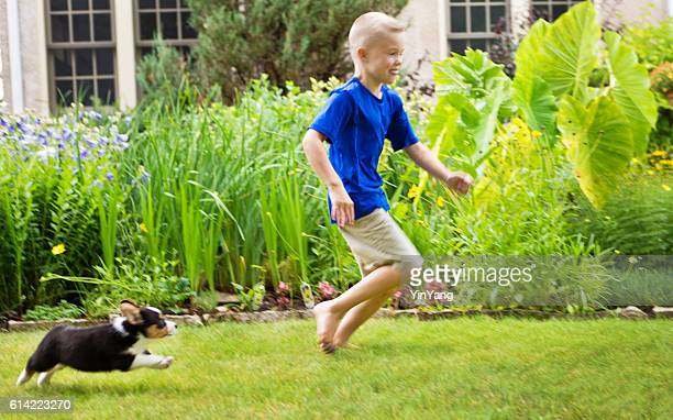 Young Boy Children Running with Puppy Dog on Lawn