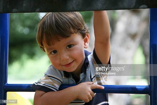 Junge Klettern auf einem Spielplatz