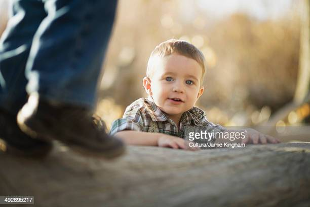 Young boy climbing on log