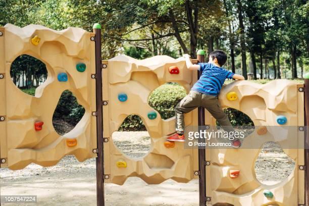 young boy climbing - peter lourenco stock-fotos und bilder