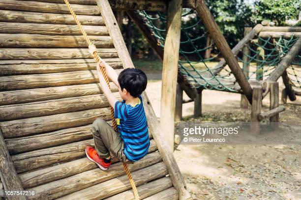 young boy climbing rope - peter lourenco stock-fotos und bilder