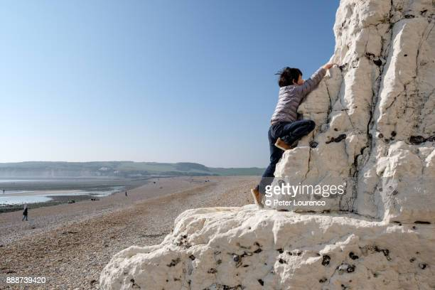 A young boy climbing up a white cliff at the beach.