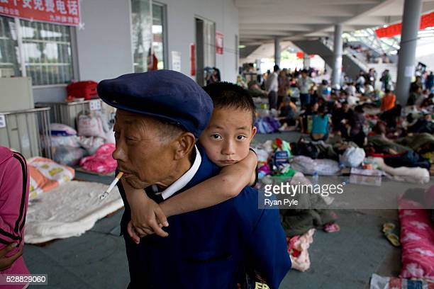 A young boy clings to his grandfather in the Mianyang Football Stadium home to over 20000 homeless earthquake survivors who have arrived over the...