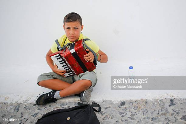 A young boy colletes money by playing a squeezebox next to the Aegon sea in the town of Fira on June 11 2015 in Santorini Greece Santorini is an...