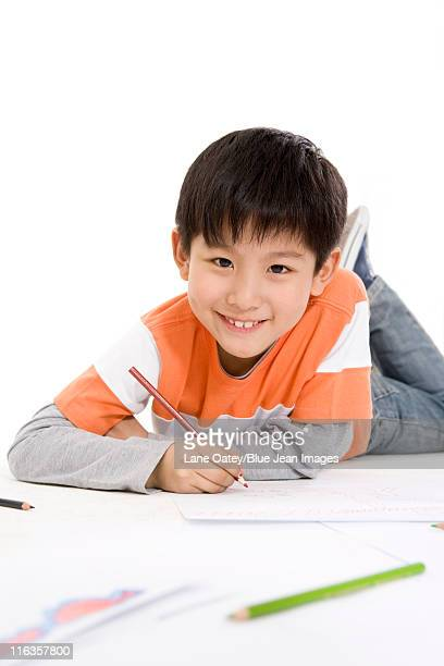 a young boy coloring while lying on the floor - pencil drawing stock pictures, royalty-free photos & images