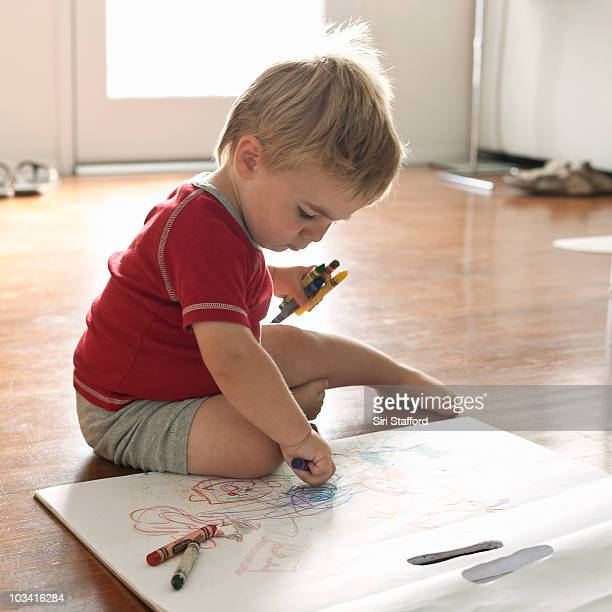 Young boy coloring while sitting on floor