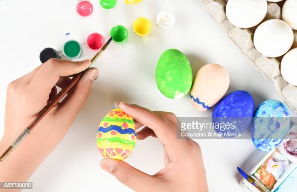 Young Boy Colouring Easter Eggs with Paintbrush Top View