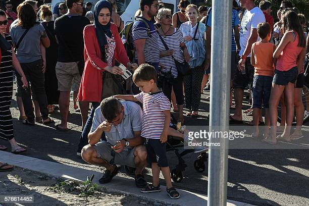 A young boy comforts to his father on the Promenade des Anglais on July 16 2016 in Nice France Five people believed to be linked to the man who...