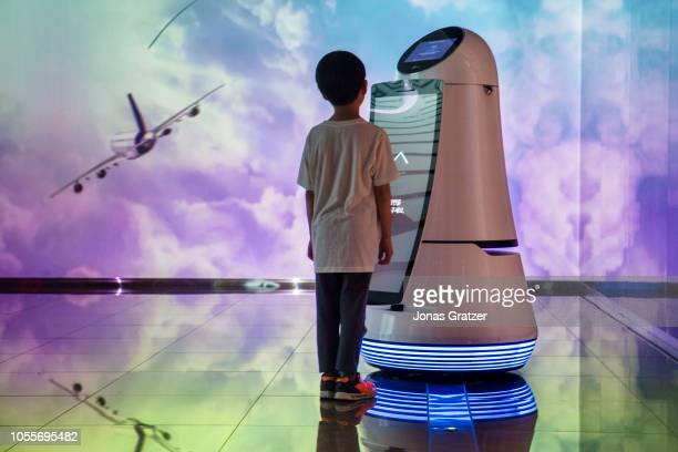 A young boy communicating with a robot that is on display at Incheon International Airport in Seoul / South Korea The Guide Robot recognises...