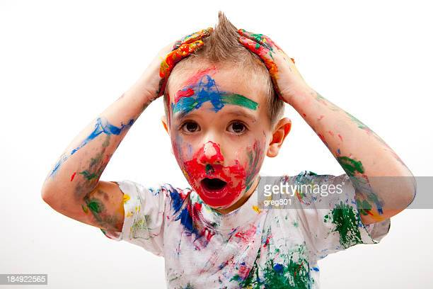 Young boy completely covered in many colors of paint