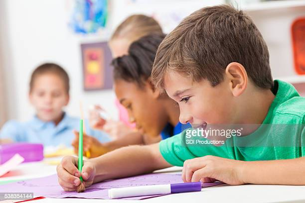 Young boy concentrates in art class