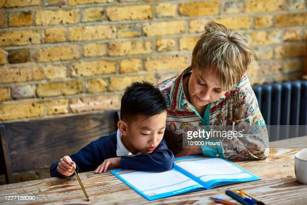 young boy concentrating on homework, with mother - spelling stock pictures, royalty-free photos & images