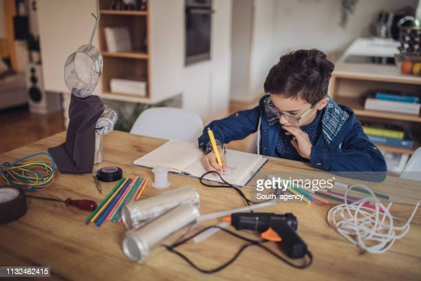 young boy constructing a robot at home - child prodigy stock pictures, royalty-free photos & images