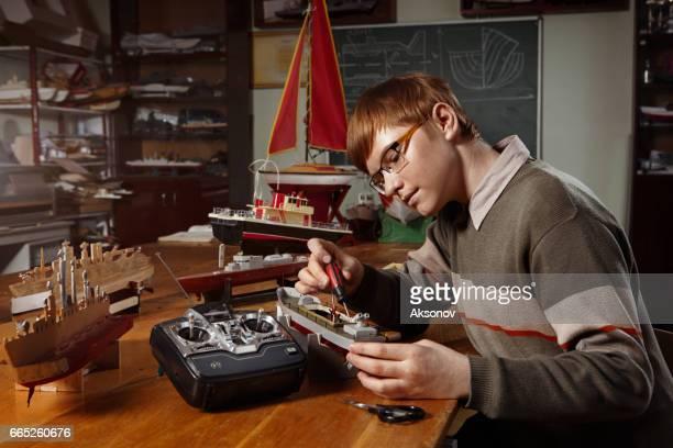 Young boy constructing a ship model