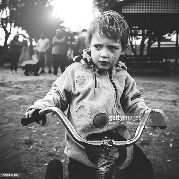 Young boy contemplating on a push bike