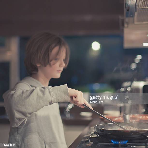 Young boy cooking behind the stove in the kitchen