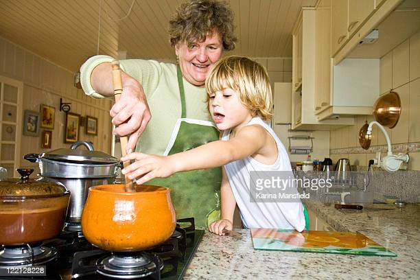Young boy cooking  with grandma