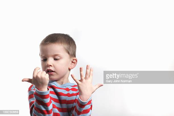 young boy counting on fingers