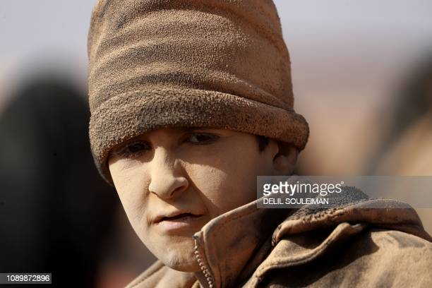 TOPSHOT A young boy covered in dust is ppictured as people who fled battles between Syrian Democratic Forces and fighters from the Islamic State...