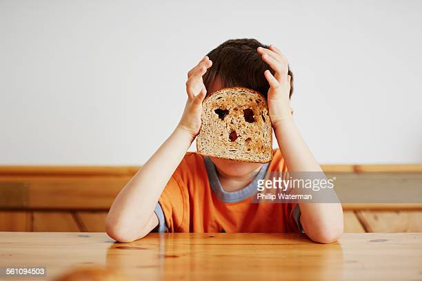 Young boy covering face with toast