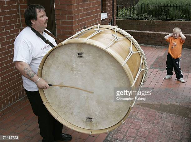 A young boy covers his ears as a man plays a Lambeg drum during preparations for the Eleventh Night Bonfires on July 11 2006 in the Sandy Row area of...