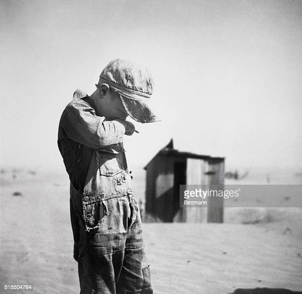A young boy covers his nose and mouth against brown sand in the Dust Bowl