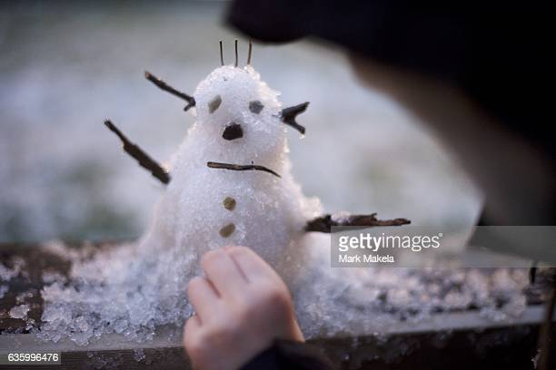 A young boy crafts a snowman on the first snowfall of the year December 17 2016 in Philadelphia Pennsylvania
