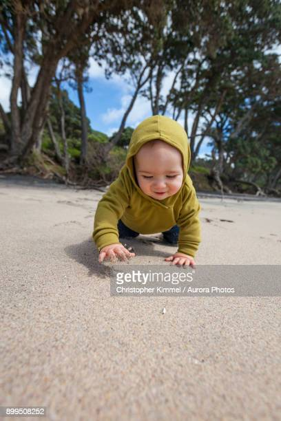 Young boy crawling at Waihi Beach in Orokawa Scenic Reserve, New Zealand