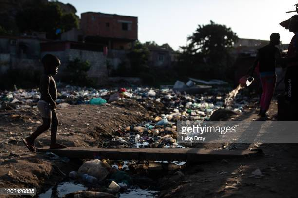 Young boy crosses a stream of sewage inside the Povoado slum on January 27, 2020 in Luanda, Angola. In June 2013, 3000 families were evicted from a...