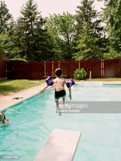 young boy curly brown short hair brown eyes jumping off diving board into pool wearing swim floats on arms in the air vertical - play off stock pictures, royalty-free photos & images