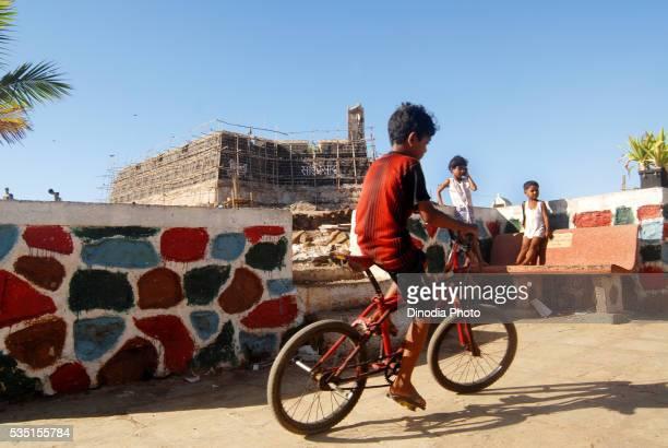 Young boy cycling at Worli village near Worli Fort in Mumbai, Maharashtra, India.