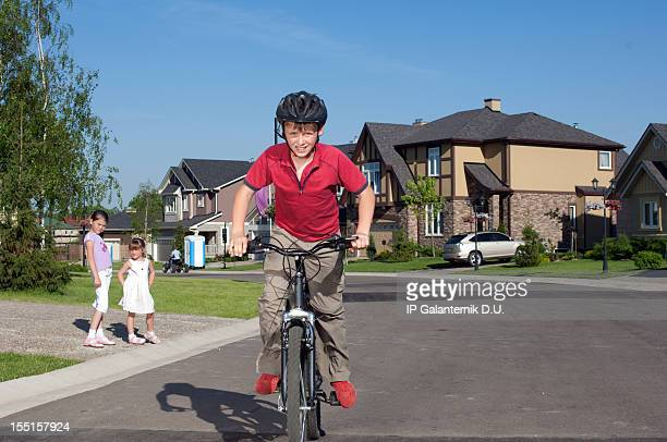 Young boy cycling by suburban street