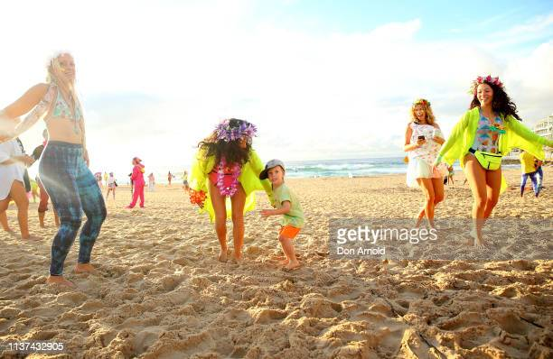 A young boy dances alongside his mother on March 22 2019 in Sydney Australia Surfers gather to celebrate five years of OneWave a not for profit that...