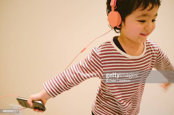 A young boy dancing wearing headphones