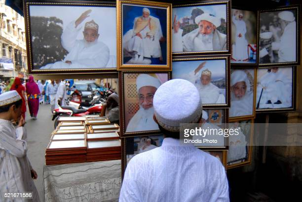 young boy dawoodi bohra muslim watch photographs of dr. syedna mohammed burhanuddin spiritual leader at bhendi bazar in bombay - indian bohra stock pictures, royalty-free photos & images