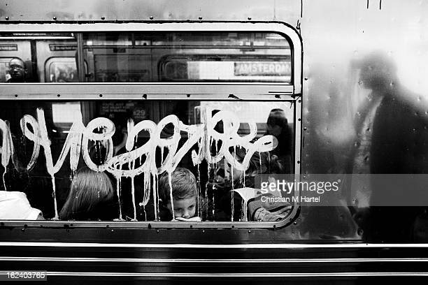 CONTENT] A young boy daydreaming on the subway seemingly not worried about his environment window covered with an acid graffiti and a silhouette of a...