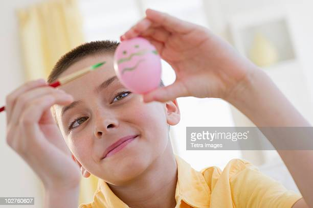 Young boy decorating an Easter egg