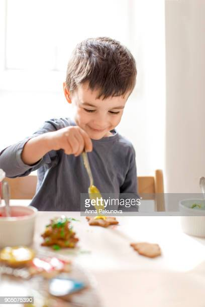 Young boy decorating cookies