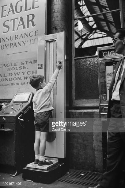 A young boy deposits his coin in a railway station weighing machine beside a signfor the Eagle Star Insurance Company England 1965 The price of using...